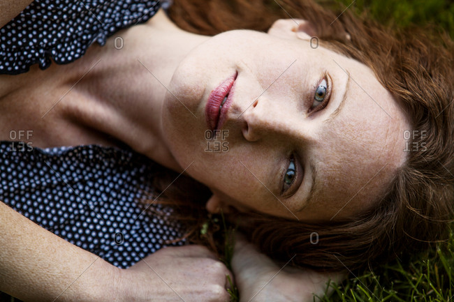Portrait of woman with auburn hair lying in grass