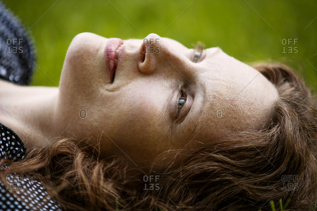 Close up of woman with auburn hair lying in grass