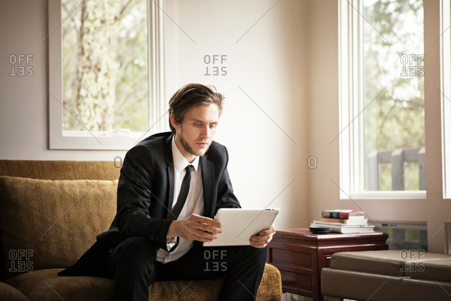 Man in suit on couch using a tablet