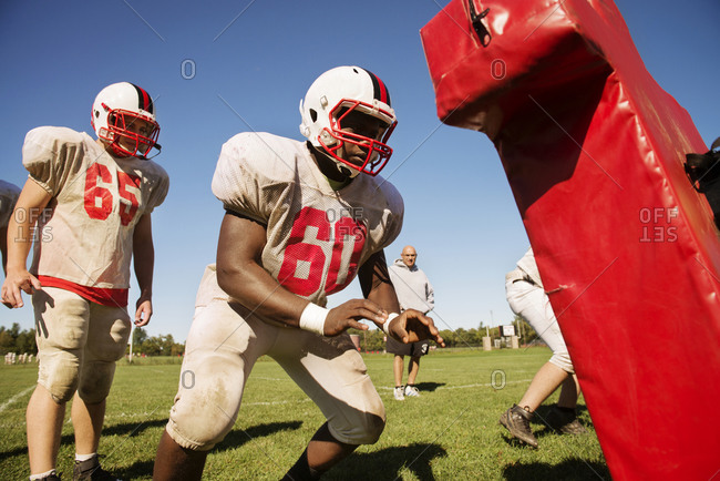 High school football players line up to practice on the tackling dummy