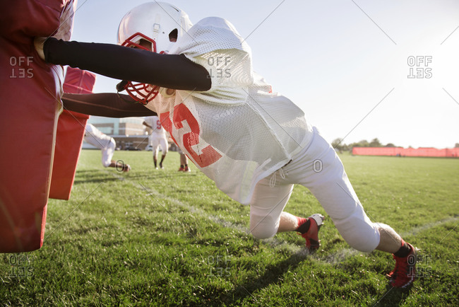 A football player pushes a tackle dummy