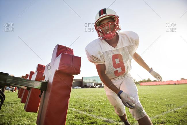 A high school football player runs past a tackling dummy
