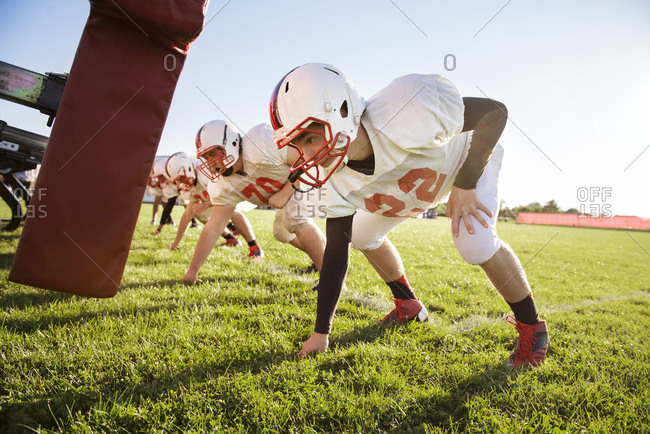 High school football players prepare to tackle a dummy