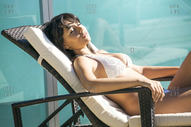 A woman relaxes on a pool chair