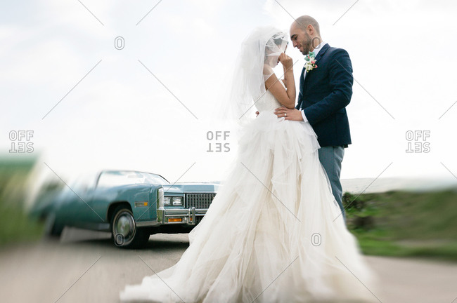 Bride and groom flirting on the road near a vintage car