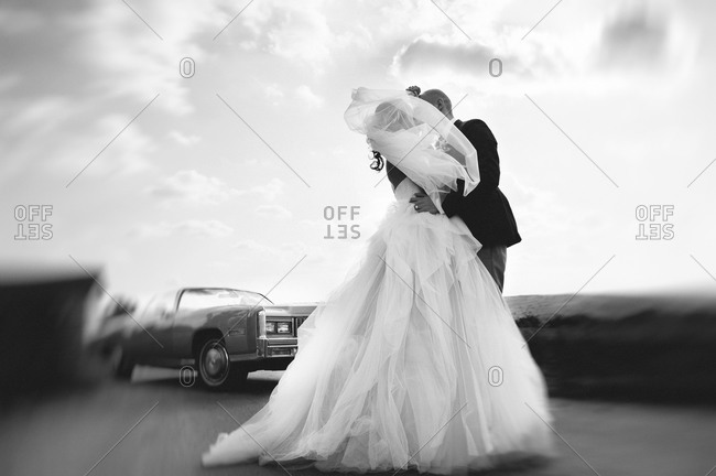 Bride and groom kissing on the road near a vintage car