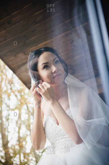 Bride putting on earrings seen through glass