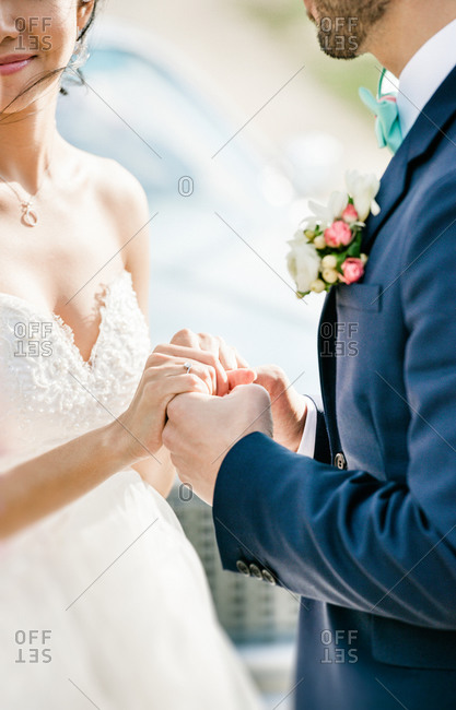 Bride and groom close on hands during personal oaths