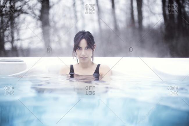 Woman in heated pool in winter