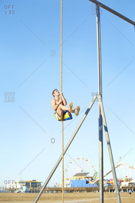 Man climbing rope at an outdoor gym
