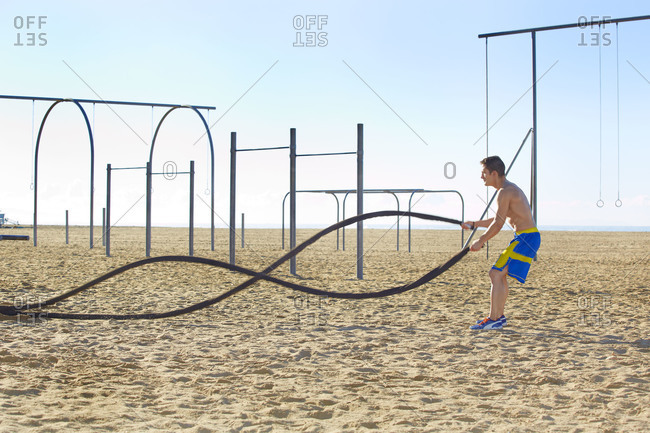 Man exercising with battling ropes