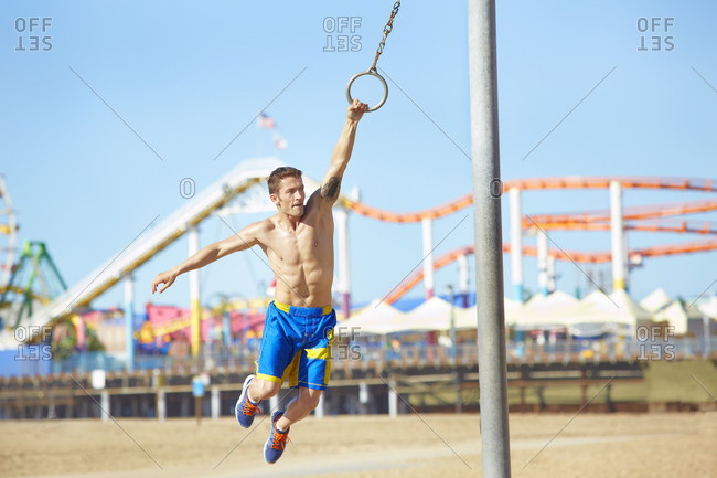 Man swinging on a ring at an outdoor gym