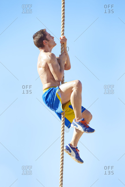 Man climbing up a rope at an outdoor gym