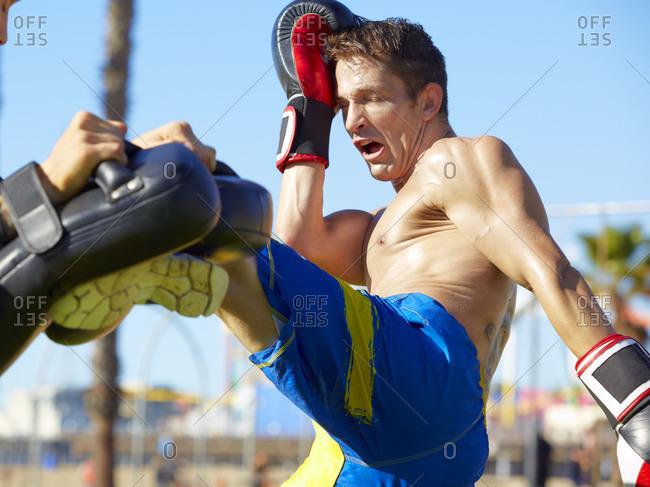 Man practicing kicks at a Muay Thai training