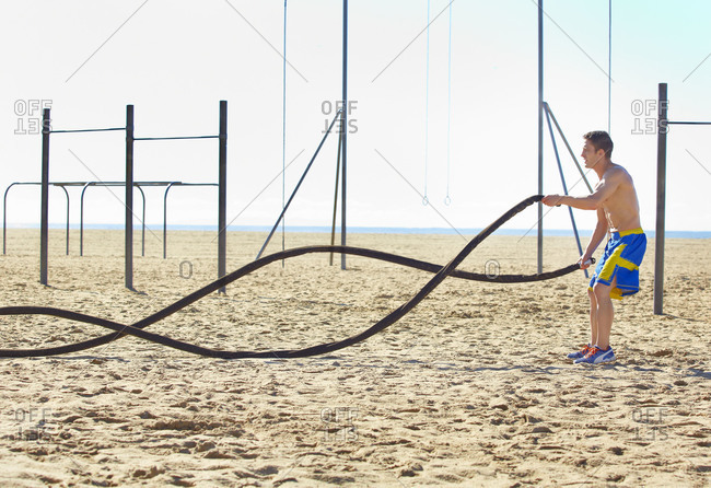 Man working out with battling ropes at an outdoor gym