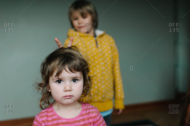 Young boy doing bunny ears behind his sister's head