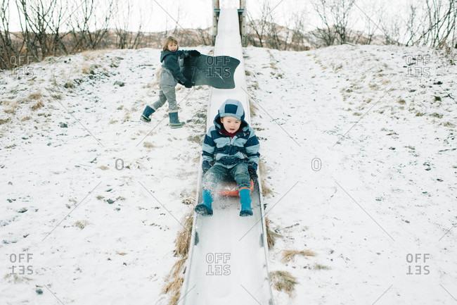 Young boys sledding on a slide