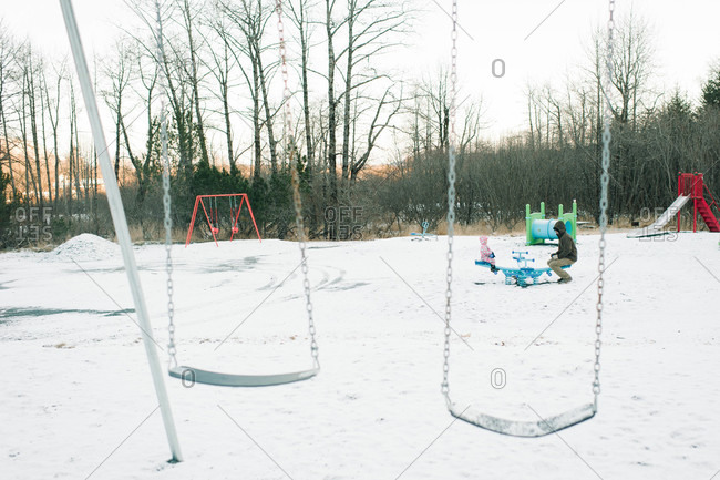 People seesawing on a snow-covered playground