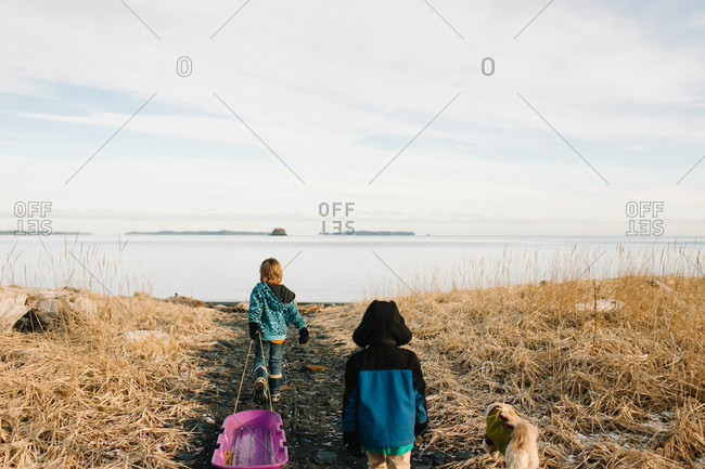 Young boy dragging a sled on a coast