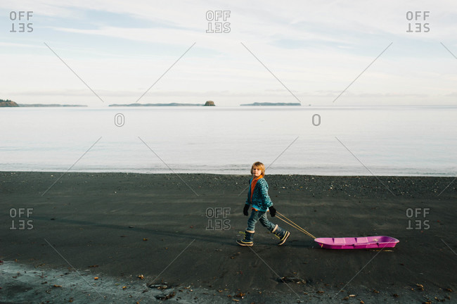 Young boy dragging a sled on a seashore