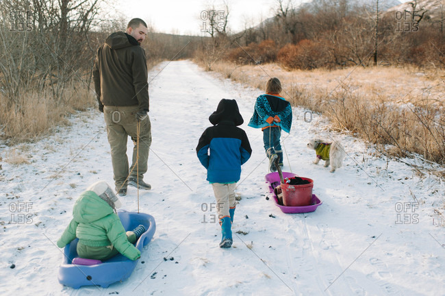 Man sledding with his children on a snow-covered road