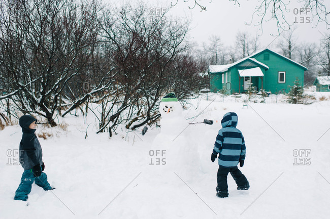 Children looking at a snowman in the backyard