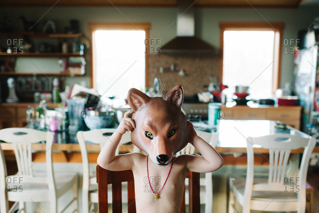 Child putting on a wolf mask