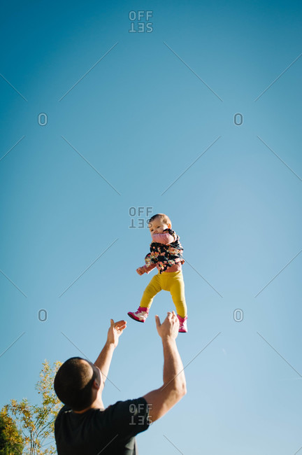 Father throwing baby in the air