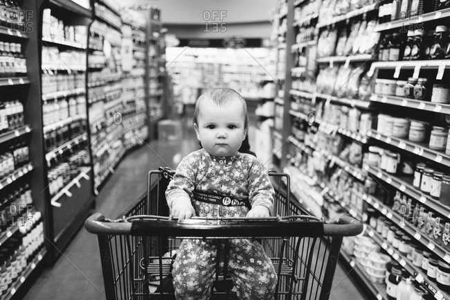Baby girl sitting in a shopping cart