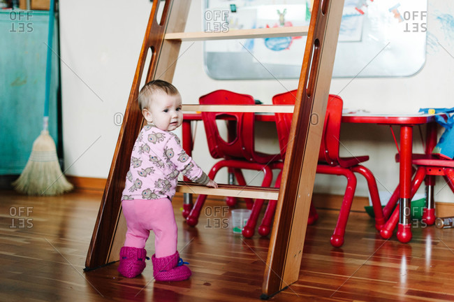 Little girl standing at the foot of a ladder