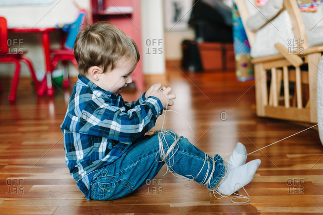 Boy wrapping twine around his legs