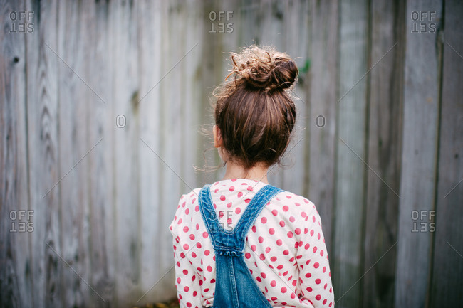Back view of a girl in overalls and polka dotted shirt