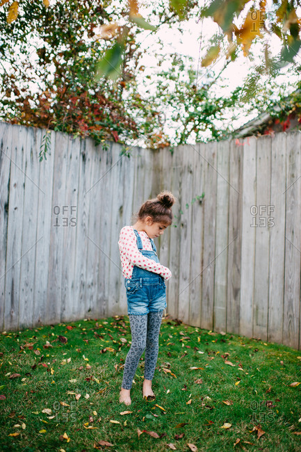 Young girl standing in the corner of fenced yard