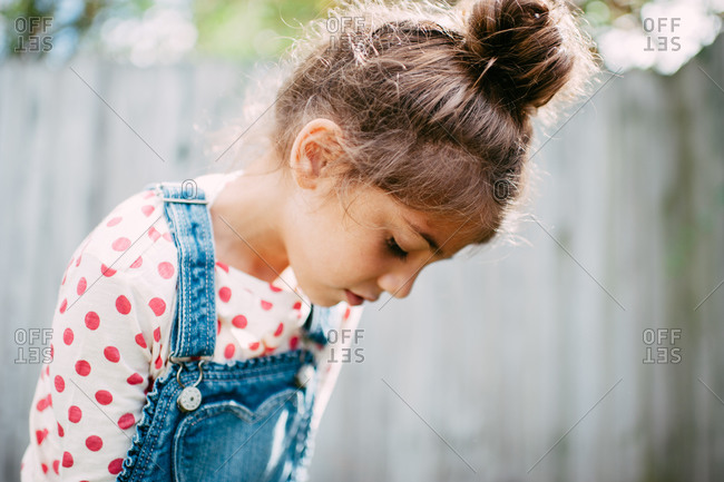 Young girl wearing a polka dotted shirt looking down