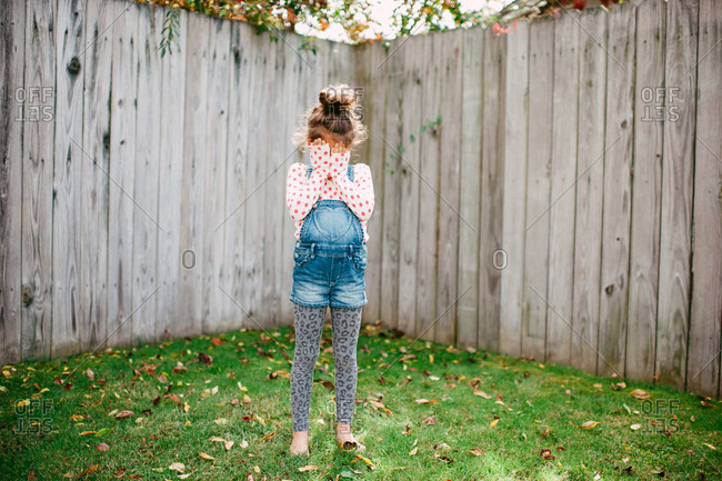 Full length shot of young girl covering her face