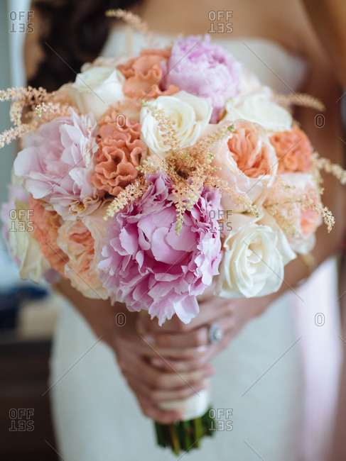 A bride holds a bouquet of flowers at a destination wedding in Phuket, Thailand