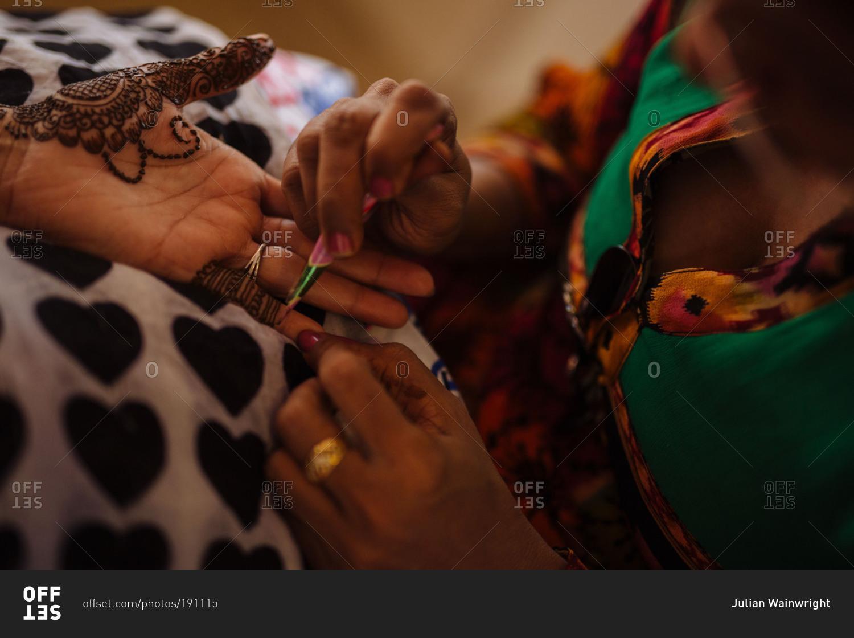 Henna Tattoo Thailand : An artist applies a henna tattoo to guest s hand at indian