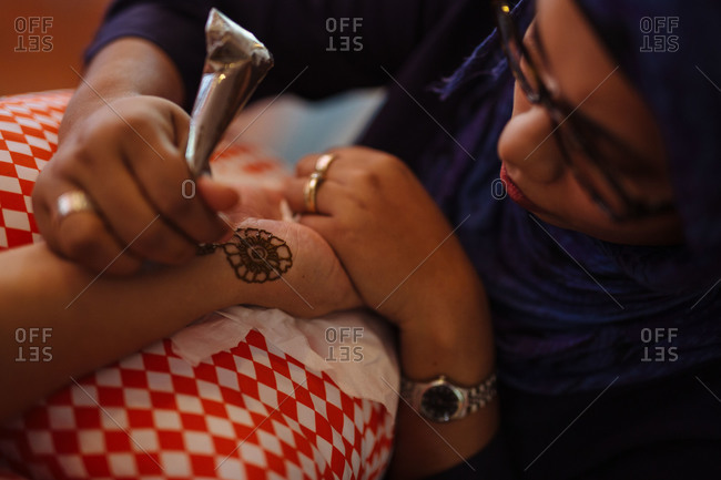 Phuket, Thailand - December 14, 2014: An artist applies a temporary henna tattoo to a guest's hand at an Indian wedding celebration