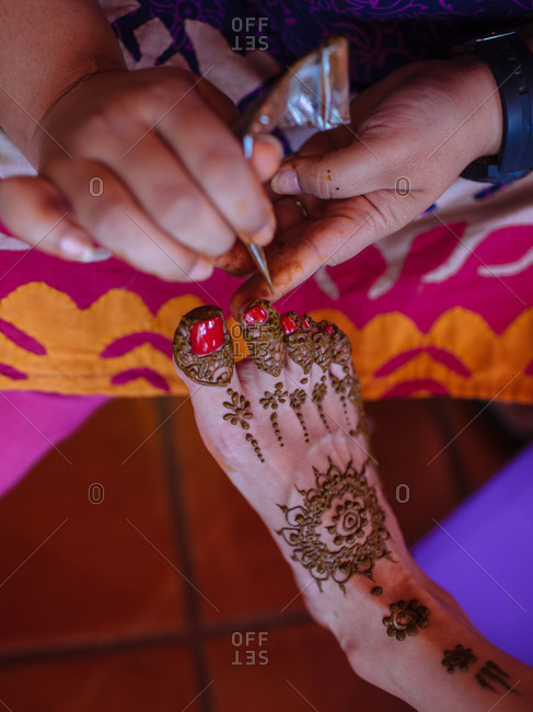 An artist applies a temporary henna tattoo to a guest's foot at an Indian wedding celebration in Phuket, Thailand
