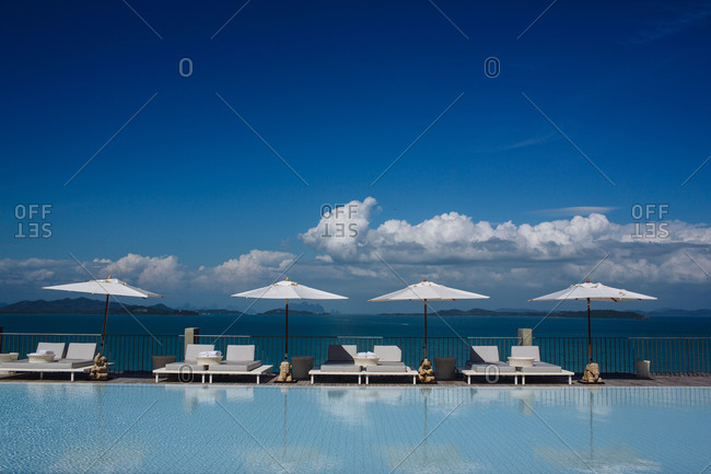 Umbrellas and chairs sit poolside at a resort in Phuket, Thailand