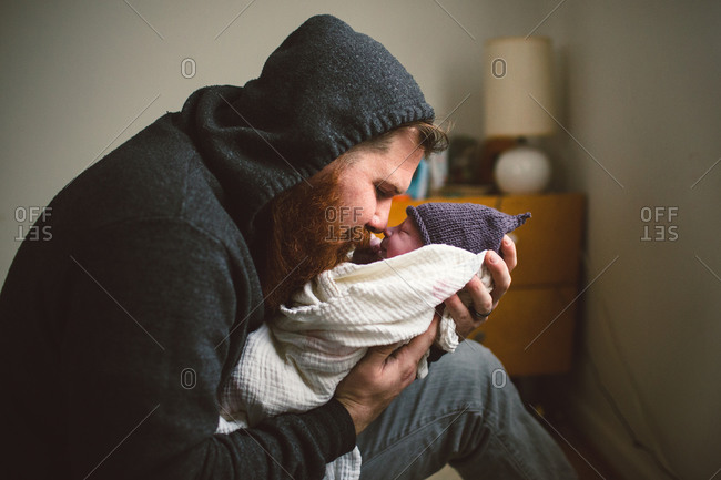 Man at home looking with admiration at newborn