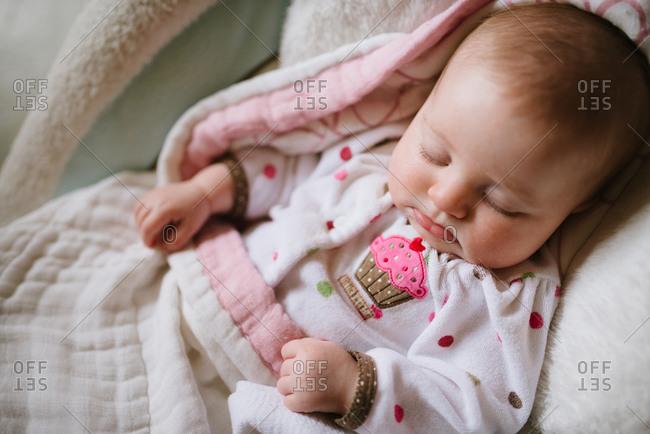 A baby in cupcake pajamas takes a nap