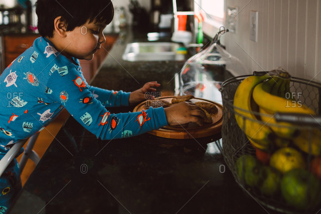 Boy helping himself to cookies on kitchen counter