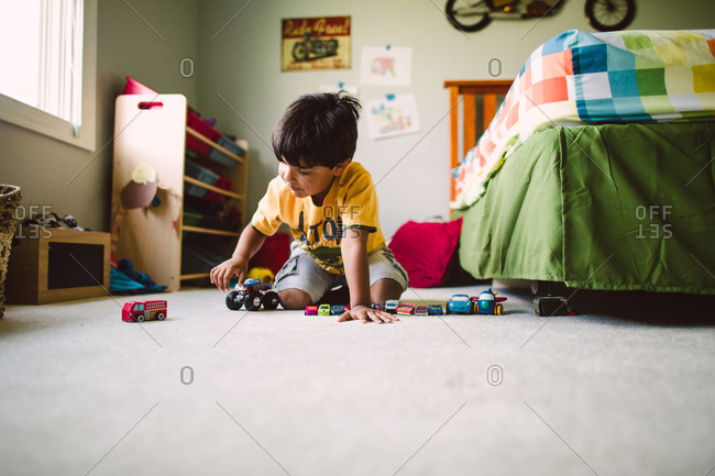 Boy playing with toy vehicles on bedroom floor