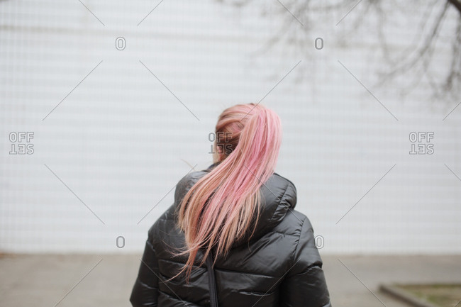 Back of woman with dyed hair walking on cold day