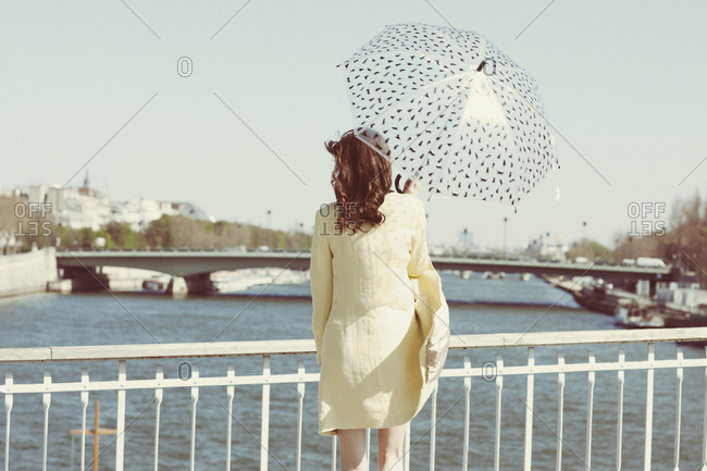 Woman with umbrella looking over river and bridges