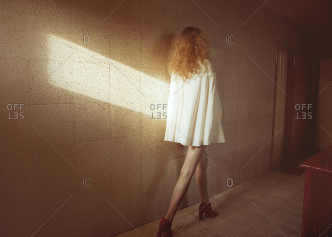 Glamorous woman waking in tiled room