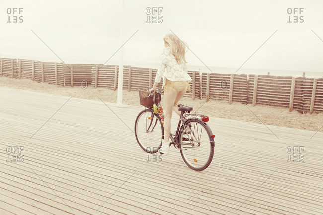 Woman riding bike along boardwalk