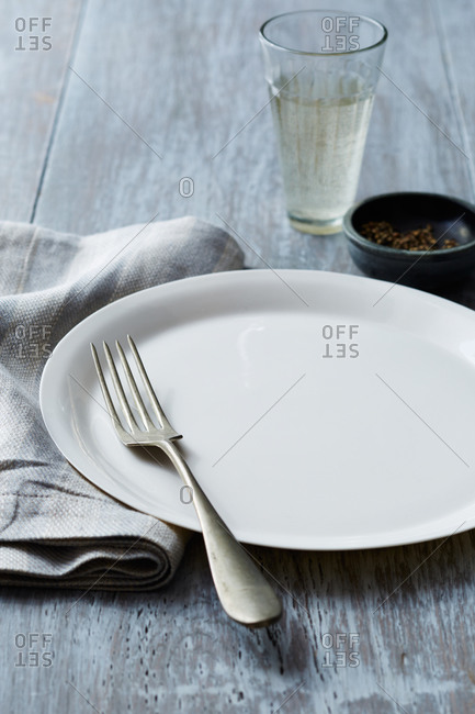 White porcelain plate and silver fork on table