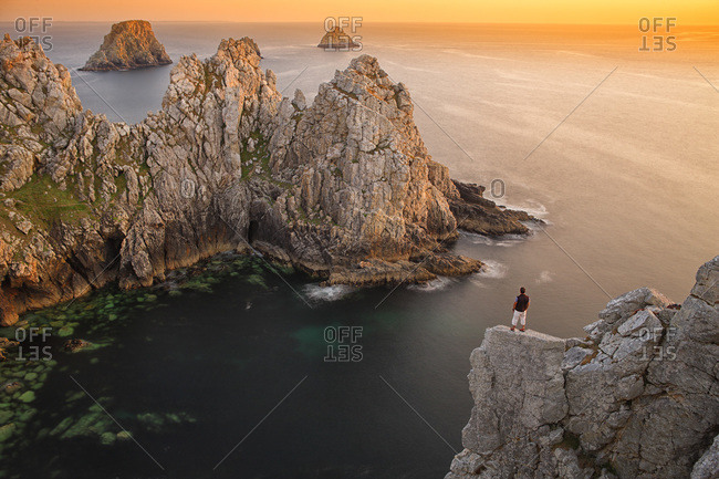 Man standing on the precipice of a rocky coast